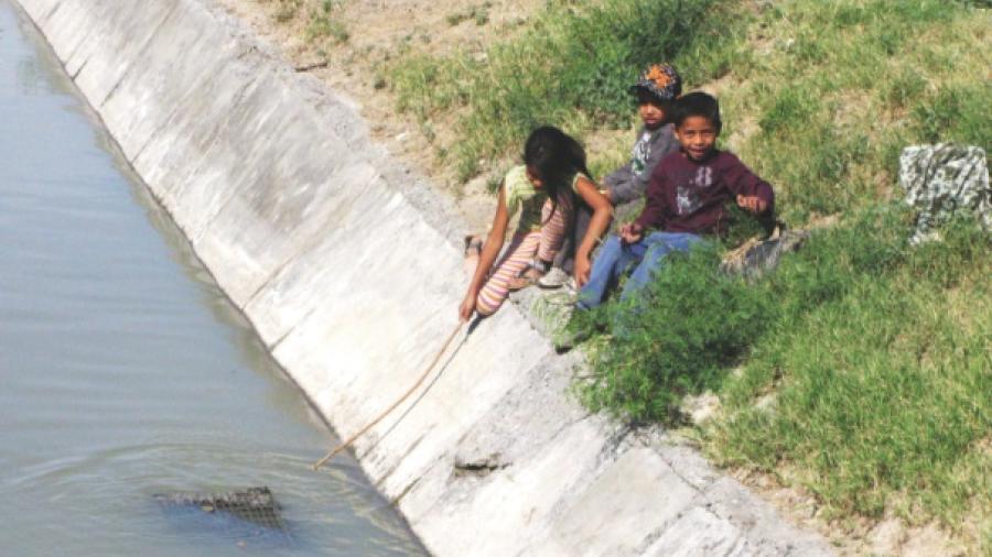 Niños juegan en canal de aguas negras